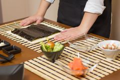 Αρχιμάγειρας γυναικών έτοιμος να προετοιμάσει τους ιαπωνικούς ρόλους σουσιών Στοκ Εικόνα
