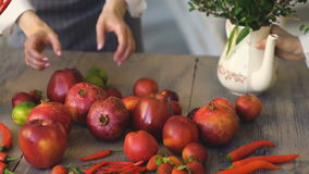 Αρχιμάγειρας γυναικών που βάζει τα φρέσκα φρούτα και λαχανικά στον ξύλινο πίνακα που προετοιμάζεται πρίν μαγειρεύει απόθεμα βίντεο