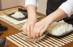 Αρχιμάγειρας γυναικών που βρέχει τα δάχτυλα στους στενούς ρόλους σουσιών Στοκ Φωτογραφία