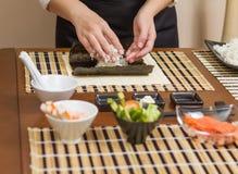 Αρχιμάγειρας γυναικών που γεμίζει τους ιαπωνικούς ρόλους σουσιών με το ρύζι Στοκ Φωτογραφίες