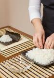 Αρχιμάγειρας γυναικών που γεμίζει τους ιαπωνικούς ρόλους σουσιών με το ρύζι Στοκ εικόνες με δικαίωμα ελεύθερης χρήσης