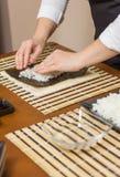 Αρχιμάγειρας γυναικών που γεμίζει τους ιαπωνικούς ρόλους σουσιών με το ρύζι Στοκ Εικόνες