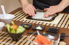 Αρχιμάγειρας γυναικών που γεμίζει τους ιαπωνικούς ρόλους σουσιών με το ρύζι Στοκ φωτογραφίες με δικαίωμα ελεύθερης χρήσης
