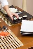 Αρχιμάγειρας γυναικών που τοποθετεί τους ιαπωνικούς ρόλους σουσιών σε έναν δίσκο Στοκ Φωτογραφία