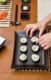 Αρχιμάγειρας γυναικών που τοποθετεί τους ιαπωνικούς ρόλους σουσιών σε έναν δίσκο Στοκ Εικόνες
