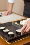 Αρχιμάγειρας γυναικών που τοποθετεί τους ιαπωνικούς ρόλους σουσιών σε έναν δίσκο Στοκ Φωτογραφίες