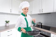 Αρχιμάγειρας γυναικών στο ομοιόμορφο τηγανίζοντας τηγάνι εκμετάλλευσης στη σύγχρονη κουζίνα Στοκ φωτογραφία με δικαίωμα ελεύθερης χρήσης