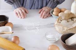 Αρχιμάγειρας δίπλα στον πίνακα κουζινών, έτοιμο να κάνει τη ζύμη Γυναίκα που φορά μια ποδιά που παίρνει έτοιμη για την παραγωγή τ στοκ φωτογραφία