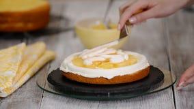 Αρχιμάγειρας ζύμης στην κουζίνα που διακοσμεί ένα κέικ Κατασκευή του κέικ με την πλήρωση ανανά απόθεμα βίντεο