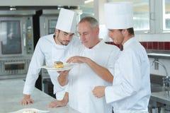 Αρχιμάγειρας και βοηθοί κατά τη διάρκεια της εργασίας στην κουζίνα Στοκ Εικόνα