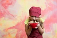 Αρχιμάγειρας κοριτσιών ή μάγειρας παιδιών στο καπέλο που τρώει τα τρόφιμα μπισκότων Στοκ εικόνα με δικαίωμα ελεύθερης χρήσης