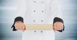Αρχιμάγειρας με την κυλώντας καρφίτσα ενάντια στη μουτζουρωμένη γκρίζα ξύλινη επιτροπή Στοκ Εικόνες
