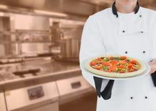 Αρχιμάγειρας με την πίτσα ενάντια στη μουτζουρωμένη κουζίνα με την πορτοκαλιά επικάλυψη Στοκ φωτογραφία με δικαίωμα ελεύθερης χρήσης