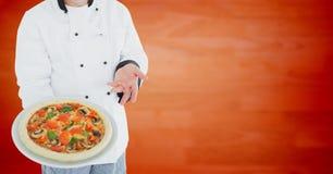Αρχιμάγειρας με την πίτσα ενάντια στη μουτζουρωμένη πορτοκαλιά ξύλινη επιτροπή Στοκ φωτογραφία με δικαίωμα ελεύθερης χρήσης