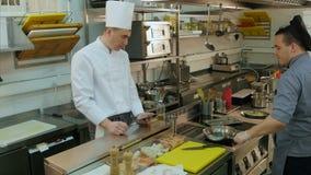 Αρχιμάγειρας με την ταμπλέτα που προσέχει το βοηθητικό μαγειρεύοντας πιάτο του σε ένα τηγάνι φιλμ μικρού μήκους