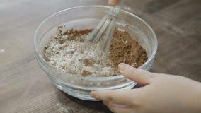 Αρχιμάγειρας που αναμιγνύει μια σκόνη κακάου με το αλεύρι στο κύπελλο φιλμ μικρού μήκους