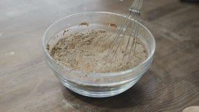 Αρχιμάγειρας που αναμιγνύει μια σκόνη κακάου με το αλεύρι στο κύπελλο απόθεμα βίντεο