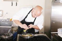 Αρχιμάγειρας που βάζει την ξυμένη παρμεζάνα σε ιταλικά ζυμαρικά Στοκ εικόνες με δικαίωμα ελεύθερης χρήσης