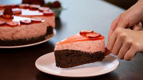Αρχιμάγειρας που βάζει το κέικ σοκολάτας φετών με mousse φραουλών στο πιάτο απόθεμα βίντεο
