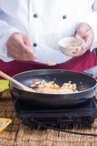Αρχιμάγειρας που βάζει το συντριμμένο φυστίκι στο τηγάνι Στοκ εικόνα με δικαίωμα ελεύθερης χρήσης
