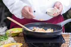 Αρχιμάγειρας που βάζει το συντριμμένο φυστίκι στο τηγάνι Στοκ εικόνες με δικαίωμα ελεύθερης χρήσης