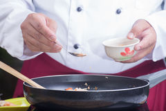 Αρχιμάγειρας που βάζει το συντριμμένο φυστίκι στο τηγάνι Στοκ Εικόνα