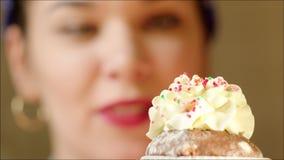 Αρχιμάγειρας που διακοσμεί Muffin με την κτυπημένες κρέμα και τη φράουλα απόθεμα βίντεο