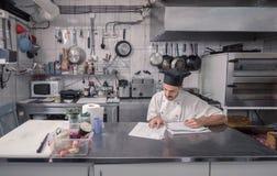 Αρχιμάγειρας που διατάζει την κουζίνα εγγράφων γραψίματος Στοκ Εικόνα