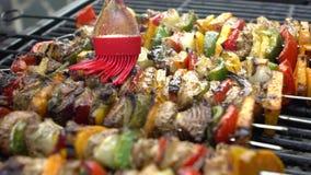 Αρχιμάγειρας που καλύπτει με τη σάλτσα τα εύγευστα οβελίδια BBQ στη σχάρα Brochette μαγειρέματος απόθεμα βίντεο