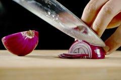 Αρχιμάγειρας που κατασκευάζει μια σαλάτα με τα κρεμμύδια Στοκ Εικόνα