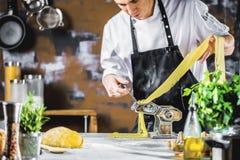 Αρχιμάγειρας που κατασκευάζει τα νουντλς μακαρονιών με τη μηχανή ζυμαρικών στον πίνακα κουζινών με μερικά συστατικά γύρω στοκ εικόνα