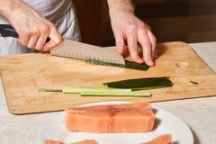 Αρχιμάγειρας που κατασκευάζει τους ρόλους σουσιών Τέμνοντα ψάρια αγγουριών και σολομών Στοκ φωτογραφία με δικαίωμα ελεύθερης χρήσης