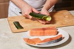 Αρχιμάγειρας που κατασκευάζει τους ρόλους σουσιών Τέμνοντα ψάρια αγγουριών και σολομών Στοκ Φωτογραφίες