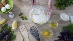 Αρχιμάγειρας που κοσκινίζει το αλεύρι πέρα από το κύπελλο γυαλιού με τα αυγά πρίν ζυμώνει, τοπ άποψη απόθεμα βίντεο