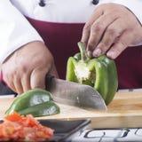 Αρχιμάγειρας που κόβει το πράσινο πιπέρι κουδουνιών με το μαχαίρι πρίν μαγειρεύει στοκ εικόνες