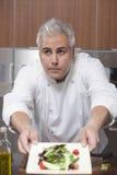 Αρχιμάγειρας που παρουσιάζει τη δευτερεύουσα σαλάτα στην εμπορική κουζίνα Στοκ Εικόνες