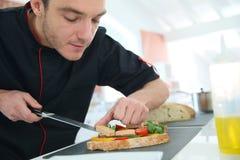 Αρχιμάγειρας που προετοιμάζει έναν εκκινητή στο εστιατόριο Στοκ Εικόνα