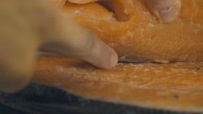 Αρχιμάγειρας που προετοιμάζει έναν φρέσκο σολομό σε έναν πίνακα κοπής, σε αργή κίνηση φιλμ μικρού μήκους