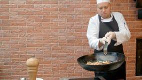 Αρχιμάγειρας που προετοιμάζει το paella με το swafood, που αναμιγνύει το πιάτο με το πετώντας τηγάνι Στοκ Εικόνες