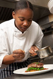 Αρχιμάγειρας που προσθέτει τη σάλτσα στο πιάτο στην κουζίνα εστιατορίων στοκ εικόνες