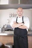 Αρχιμάγειρας που στέκεται δίπλα στην κουζίνα στην κουζίνα στοκ φωτογραφίες