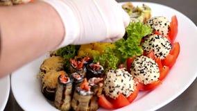 Αρχιμάγειρας που τακτοποιεί το μαριναρισμένο κουνουπίδι στο πιάτο με τα ψημένα τρόφιμα φιλμ μικρού μήκους