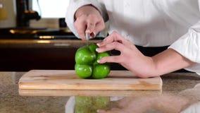 Αρχιμάγειρας που τεμαχίζει ή που κόβει το πράσινο πιπέρι κουδουνιών στον τέμνοντα πίνακα απόθεμα βίντεο