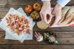 Αρχιμάγειρας που τρίβει το σκόρδο σε μια φέτα ψωμιού Στοκ εικόνες με δικαίωμα ελεύθερης χρήσης