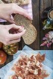 Αρχιμάγειρας που τρίβει το σκόρδο σε μια φέτα ψωμιού Στοκ Εικόνες