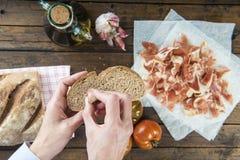 Αρχιμάγειρας που τρίβει το σκόρδο σε μια φέτα ψωμιού Στοκ εικόνα με δικαίωμα ελεύθερης χρήσης