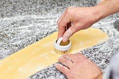 Αρχιμάγειρας που χρησιμοποιεί την τέμνουσα μορφή μετάλλων ζύμης Στοκ Φωτογραφία