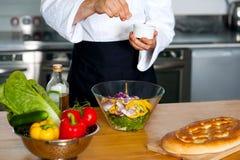 Αρχιμάγειρας που ψεκάζει το άλας στα λαχανικά στοκ φωτογραφία
