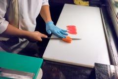 Αρχιμάγειρας σουσιών που τεμαχίζει μια ακατέργαστη φρέσκια λωρίδα σολομών με ένα αιχμηρό μαχαίρι Στοκ Εικόνες