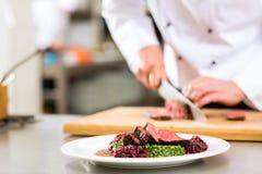 Αρχιμάγειρας στην κουζίνα εστιατορίων που προετοιμάζει τα τρόφιμα Στοκ εικόνα με δικαίωμα ελεύθερης χρήσης